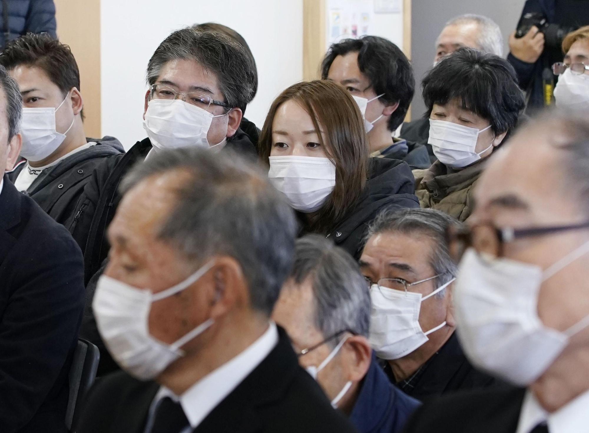 People wearing masks as they attend a memorial for victims of the Great East Japan Earthquake held Sunday in Iwaki, Fukushima Prefecture. | KYODO
