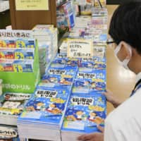 Workbooks for children are stacked up at a bookstore in Tokyo last week as the nationwide school closures got underway.   KYODO