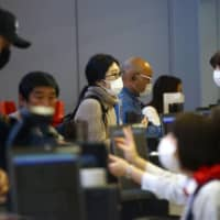 Passengers wearing protective masks check in at Kansai International Airport in Osaka. In just a matter of weeks, people in affected areas have become accustomed to wearing masks, stocking up on essentials, canceling social and business gatherings, scrapping travel plans and working from home.  | REUTERS