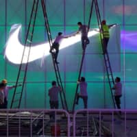 Workers install a Nike logo lamp outside the Wukesong Arena in Beijing in August last year. | REUTERS
