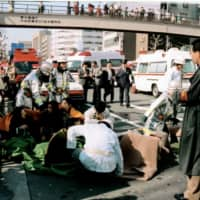 Patients receive treatment in front of Tsukiji Station in Tokyo on March 20, 1995, after a sarin gas attack by the Aum Shinrikyo cult.   KYODO