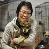 Wanspace founder and president Mie Suzuki hugs Megane, a puppy who got his name from the folds of skin around his eyes in February. Megane means 'glasses' in Japanese. | KYODO