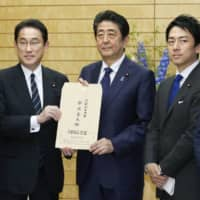 Prime Minister Shinzo Abe receives a set of proposals from Fumio Kishida (left), policy chief of Abe's Liberal Democratic Party, on May 21. | KYODO