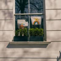 Over the rainbow: Hand-painted art is displayed in the window of a home in London during a city-wide lockdown caused by the rapid spread of COVID-19. Non-Japanese residents in Japan receiving word of the situation from family and friends overseas are likely to feel stress due to their inability to help out.  | BLOOMBERG