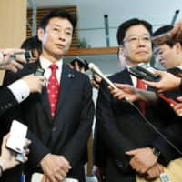 Yasutoshi Nishimura (left), the economic policy minister in charge of coronavirus measures, and health minister Katsunobu Kato face reporters at the Prime Minister's Office on Thursday. | KYODO