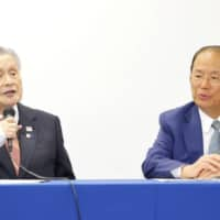 Yoshiro Mori (left), head of the Tokyo Organising Committee, and Toshiro Muto, the committee's chief executive, hold a news conference Tuesday following a telephone conference with International Olympic Committee President Thomas Bach. | KYODO