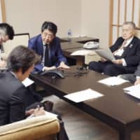Prime Minister Shinzo Abe, President of the Tokyo Organising Committee Yoshiro Mori, Tokyo Gov. Yuriko Koike, Olympic Minister Seiko Hashimoto and Chief Cabinet Secretary Yoshihide Suga hold a telephone conference with International Olympic Committee President Thomas Bach at Abe's official residence in Tokyo on Tuesday. | CABINET PUBLIC RELATIONS OFFICE / VIA KYODO