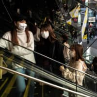 People wearing masks browse in a shopping mall in Tokyo earlier this month. | REUTERS