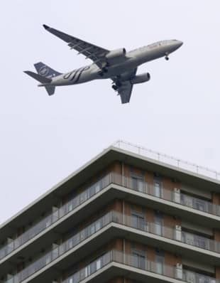 An airplane flies over central Tokyo in a test of the new flight paths for international passenger aircraft bound for Haneda Airport in February. | KYODO