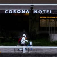 A man passes in front of the Corona Hotel in the city of Osaka on March 14. | REUTERS