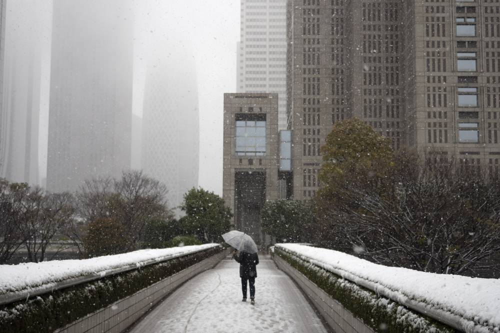 A solitary individual walks along a bridge as snow falls Sunday in Tokyo. Gov. Yuriko Koike has asked the city's 13 million residents to stay home this weekend, saying the capital is on the brink of an explosion in coronavirus infections. | AP