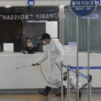A worker sprays disinfectant as a precaution against the new coronavirus at the main railway station in Seoul on Sunday.   AP