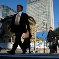 Pedestrians walk past the Bank of Japan (BOJ) headquarters in Tokyo, Japan, on Friday, Jan. 4, 2019. Japan's benchmarkbond yieldfell to the lowest in more than two years on Friday as a stronger yen and a slowdown inglobal manufacturingspurred demand for the assets as a haven. | BLOOMBERG