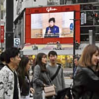 A large screen at the famous scramble crossing in Tokyo's Shibuya district shows Gov. Yuriko Koike calling on residents to refrain from going outside to fight a surge in coronavirus cases in the capital. | KYODO
