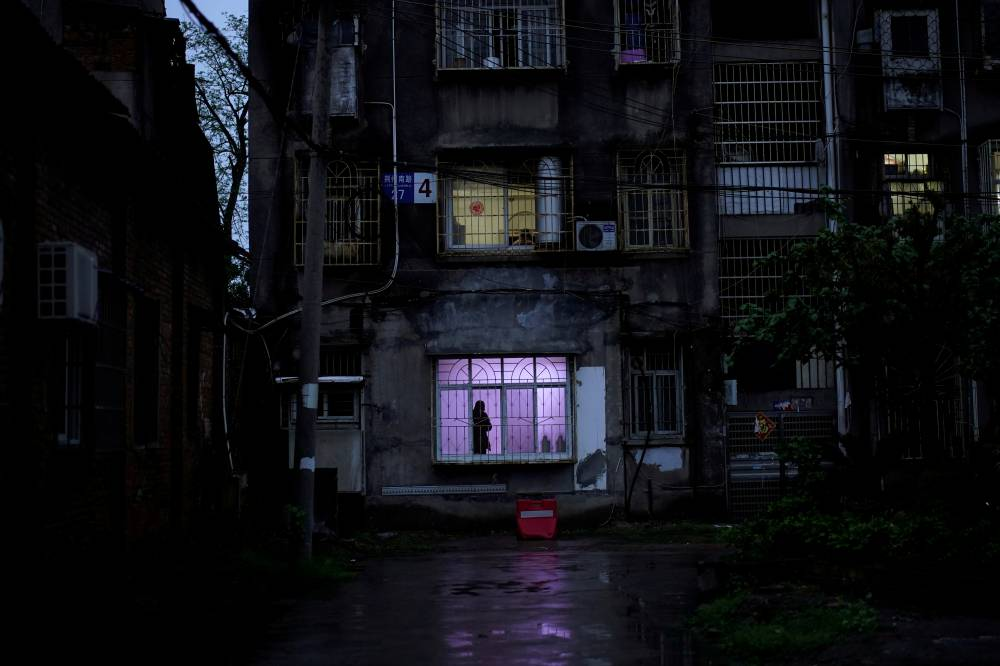 A man stands near a window in a residential community in Jingzhou on Friday, after the coronavirus lockdown was eased in Hubei province.  | REUTERS