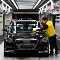 An employee performs final inspections on a Hyundai Motor Co. Genesis luxury sedan on the production line at the company's plant in Ulsan, South Korea, in 2017. | BLOOMBERG
