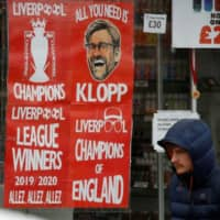 A man walks past Liverpool posters in a shop window in Liverpool, England, on March 18.  | REUTERS