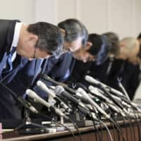 Kansai Electric Power Co.'s new president Takashi Morimoto (second from left) and his predecessor Shigeki Iwane (left) bow in apology during a press conference in Osaka on March 14. | KYODO