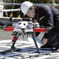 A postman checks a drone for mail delivery during a recent experiment in a Tokyo suburb. | KYODO