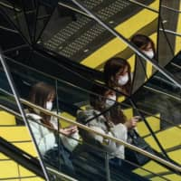Women wearing face masks are reflected in mirrors at a shopping arcade in Tokyo's Harajuku district Monday. | AFP-JIJI