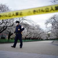 Self-restraint, please: A security person stands guard at the famed street of cherry blossoms in Tokyo's Ueno Park, which is closed as a safety precaution against the new coronavirus. | AP