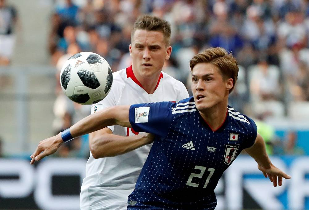 Japan's Gotoku Sakai battles for the ball with Poland's Piotr Zielinski during the 2018 FIFA World Cup on June 28, 2018, in Volgograd, Russia. | REUTERS