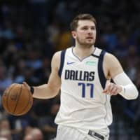 Mavericks guard Luka Doncic handles the ball against the Nuggets on March 11 in Dallas. | AP