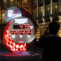 A passerby takes photos of a countdown clock in front of Tokyo Station on Monday showing the adjusted days and time for the start of the postponed Tokyo Olympic Games, which are now set to begin on July 23, 2021.  | KYODO