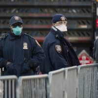 New York City police officers wear protective gear while monitoring people waiting in line to be tested for coronavirus disease outside Elmhurst Hospital Center in the Queens borough of New York City on Thursday.  | REUTERS