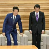 Prime Minister Shinzo Abe, center, and Deputy Prime Minister Taro Aso, right, attend a Cabinet meeting on Tuesday in Tokyo.  | KYODO