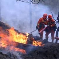 Firefighters on Tuesday work on extinguishing a forest fire that started near Xichang in Liangshan prefecture of Sichuan province, China. | CHINA DAILY / VIA REUTERS