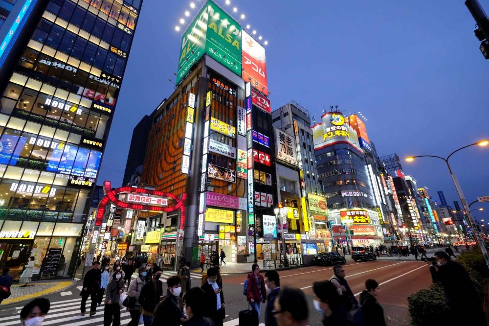 People cross a street at Tokyo's entertainment district Kabukicho on Tuesday. | AFP-JIJI