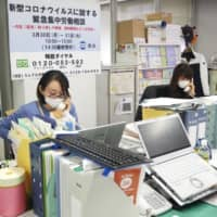 A worker at the Japanese Trade Union Confederation takes calls from people whose jobs have been affected by the novel coronavirus on Tuesday in Tokyo.  | KYODO
