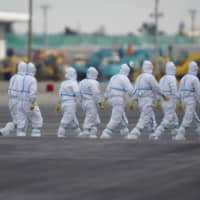 Heading in: Workers in protective gear prepare to board the Diamond Princess cruise ship on Feb. 7. The Japanese government has come under some criticism for not heeding the advice of infectious diseases experts when it comes to its response to the spread of the new coronavirus, COVID-19. | BLOOMBERG