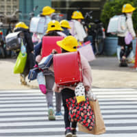 Sudden last day: Students leave school with many bags on Feb. 28 after it was announced that schools in Japan would close in March to try to stop the spread of the new coronavirus. | KYODO