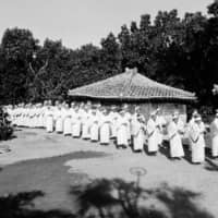 At the last: The women of Kudaka Island, dressed in white robes during the Izaiho ceremony, lead a procession across the island, December 1978 | HIROAKI YAMASHIRO