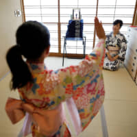 A mother and daughter take an online dance lesson in their Tokyo home March 17. | REUTERS