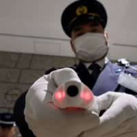 A security guard shows a body temperature-measuring device at the reception of the Tokyo Metropolitan Government office in Tokyo on Thursday. Japan will quarantine all passengers arriving from China and South Korea, the country's prime minister said on March 5. | AFP-JIJI