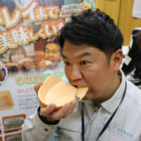 Katsuhiko Sakakibara, the managing director of confectionery firm Marushige Seika bites into an oval e-tray plate, one of the company's edible tableware products. | KYODO