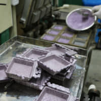 Freshly made square e-tray plates are ready to be trimmed at Marushige Seika. | KYODO