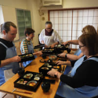 Getting a culinary education: Elizabeth Andoh helps participants arrange a bento during one of her washoku cooking classes held in Tokyo. | JOAN BAILEY