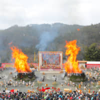 After lighting, bright orange flames burst out of the two gomadan pyres at the center of the amphitheater at the Agon Shu Fire Rites Festival in Kyoto on Feb. 9. | AGON SHU