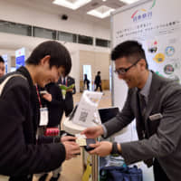 A high school student exchanges his business card with a company representative during a Student Ambassador Program workshop at Pacifico Yokohama. | YOSHIAKI MIURA
