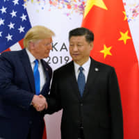 U.S. President Donald Trump and Chinese President Xi Jinping pose for photographers ahead of their bilateral meeting during the Group of 20 summit in Osaka last June 29. Trump has taken a personal approach in his engagements with powerful foreign leaders . | REUTERS