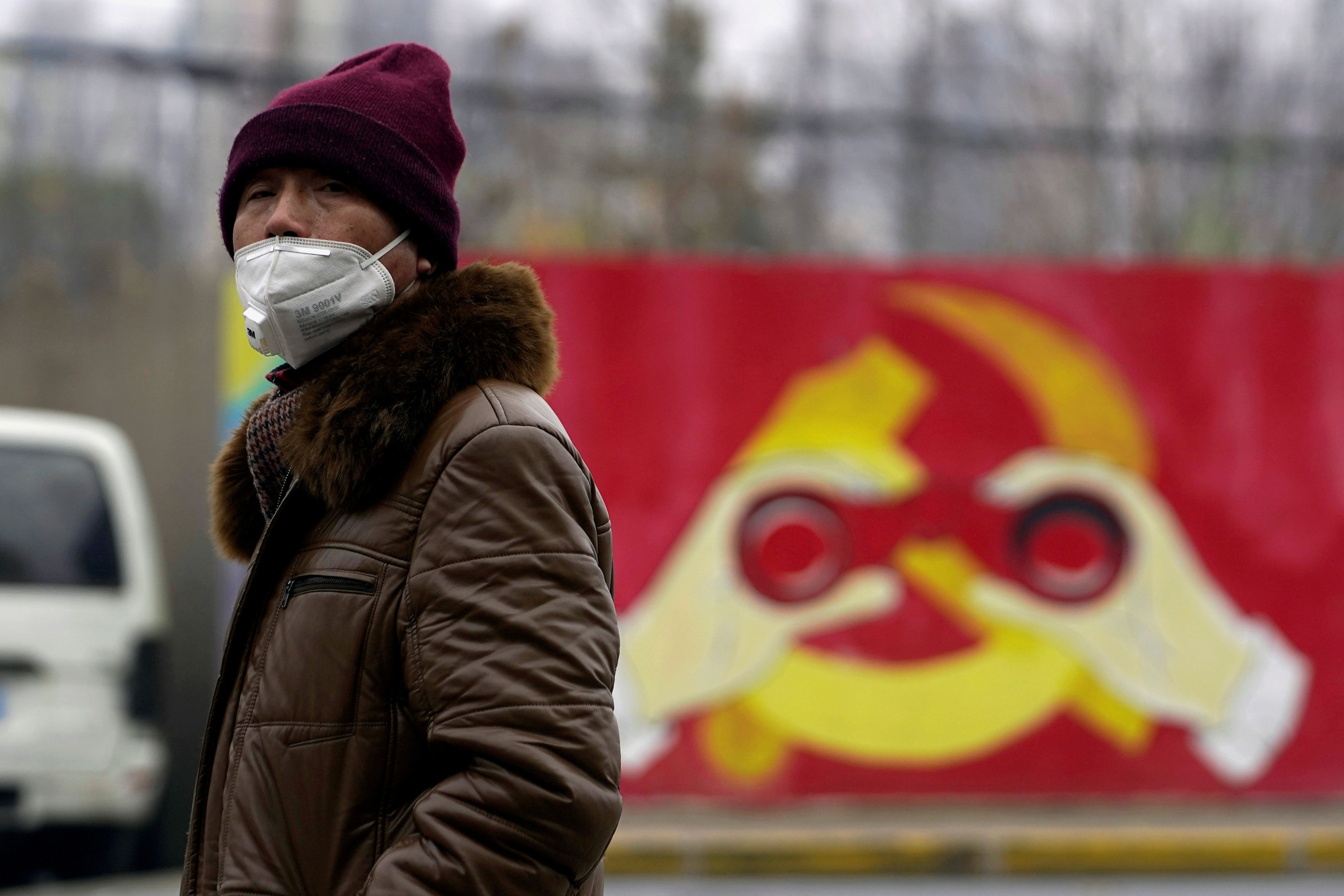 A man walks past a mural in Shanghai showing a modified image of the Chinese Communist Party emblem. | REUTERS