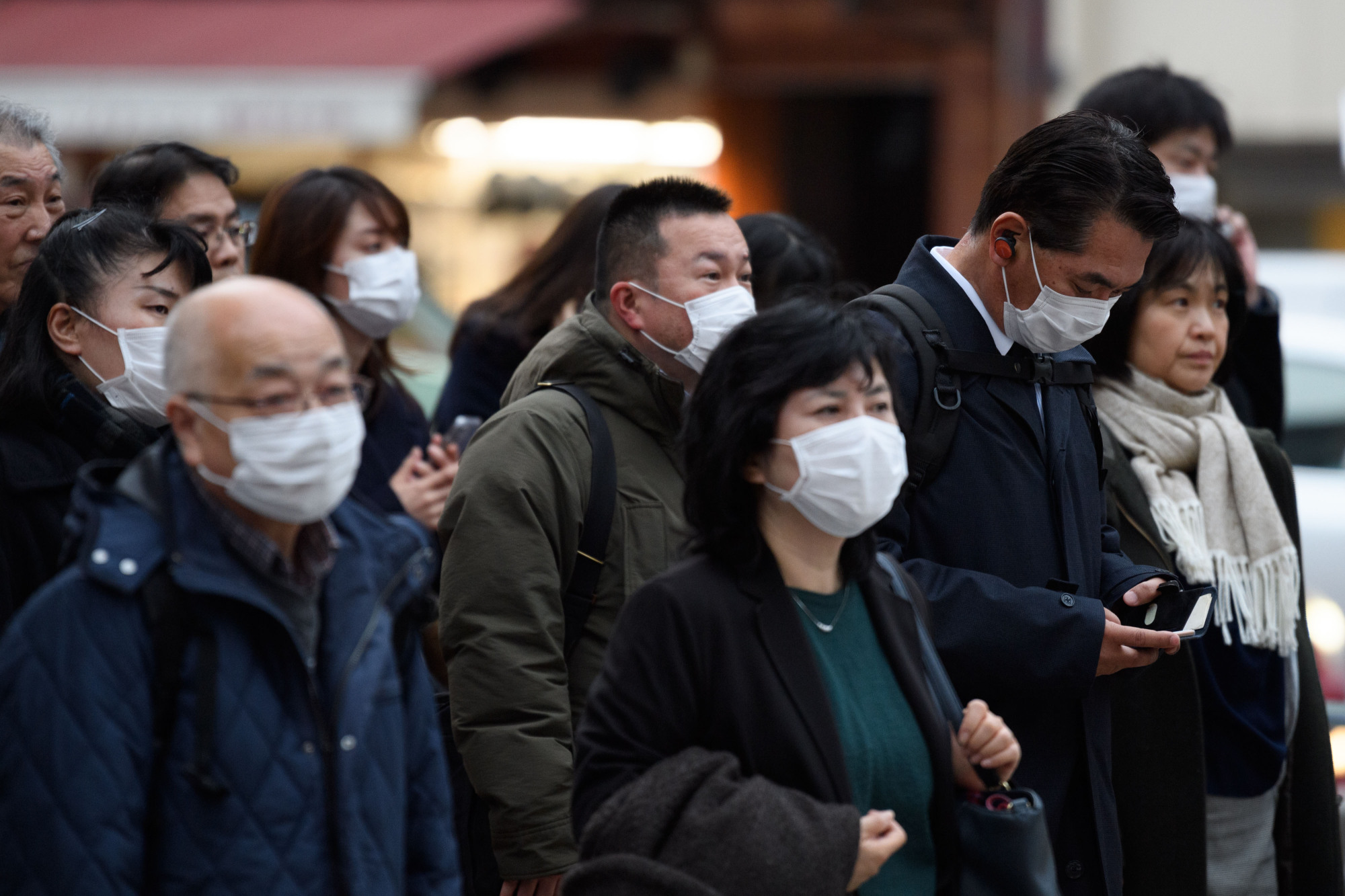 Pedestrians wearing protective masks wait to cross a road in Tokyo on Monday. The government must disseminate more  information on the outbreak in foreign languages. | BLOOMBERG