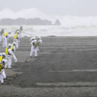 Police officers search for the remains of people who went missing in the March 2011 Great East  Japan Earthquake and tsunami on March 10 in  Sendai, Miyagi Prefecture. | REUTERS