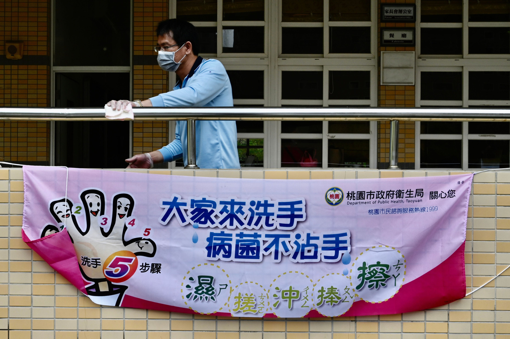 A man cleans a handrail at a middle school in Taoyuan, northern Taiwan, on Saturday behind a sign telling students how to wash their hands to prevent the transmission of COVID-19. | AFP-JIJI