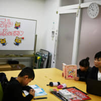Mayumi Iijima, shown on Friday, is fortunate that her Tokyo-based firm is allowing her to bring her young children to work while their school is closed due to the COVID-19 outbreak. | AFP-JIJI