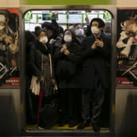 Commuters wearing masks stand in a packed train at Shinagawa Station on March 2. | AP